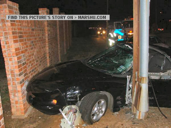 firebird car crash: outside car front with telephone pole and brick wall. You can see emergency workers in background